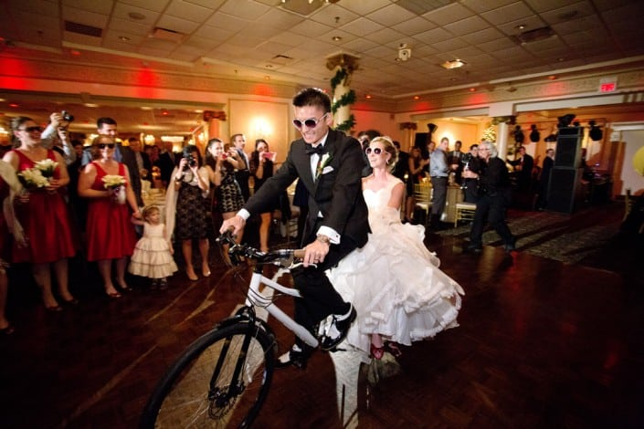 Bride and groom enters their wedding reception with a tandem bike at Primavera Regency, NJ