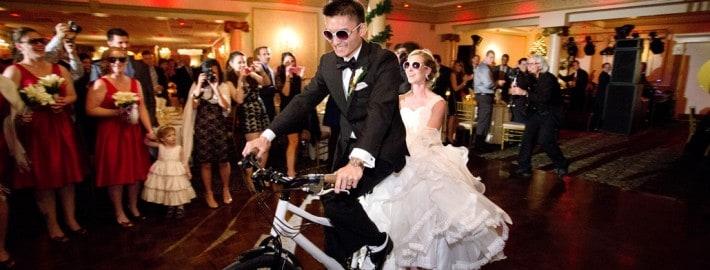 Bride and groom enters their wedding reception with a tandem bike at Primavera Regency, NJ