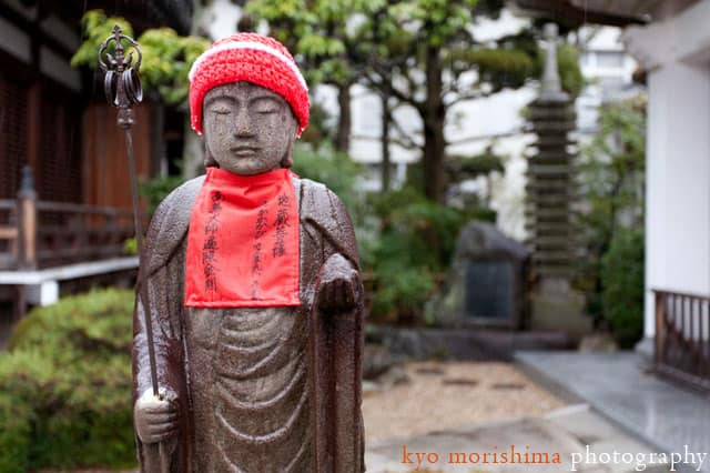 A stone statue wearing a knit cap at the Buddhist temple in Takarazuka, Japan, photographed by Kyo Morishima