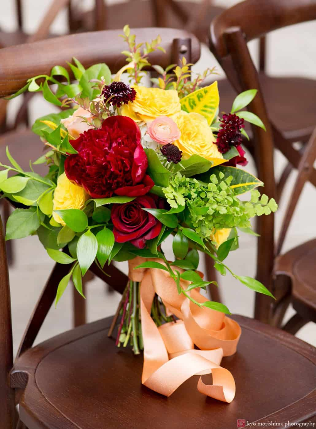 Colorful maroon and gold bouquet with dark red roses and peonies, yellow roses, pale blush ranunculus, ruby scabiosa, and croton petra leaves, tied with apricot ribbon. Wedding bouquet by Kristin Rockhill of Details of I Do, photographed by Kyo Morishima