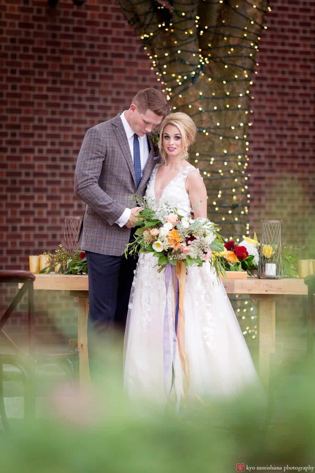 """Bride wearing Ariane wedding gown from BHLDN with groom in front of West Elm table on back patio at Nassau Inn """"Madmen"""" photo shoot styled by Kristin Rockhill of Details of I Do, photographed by Kyo Morishima"""
