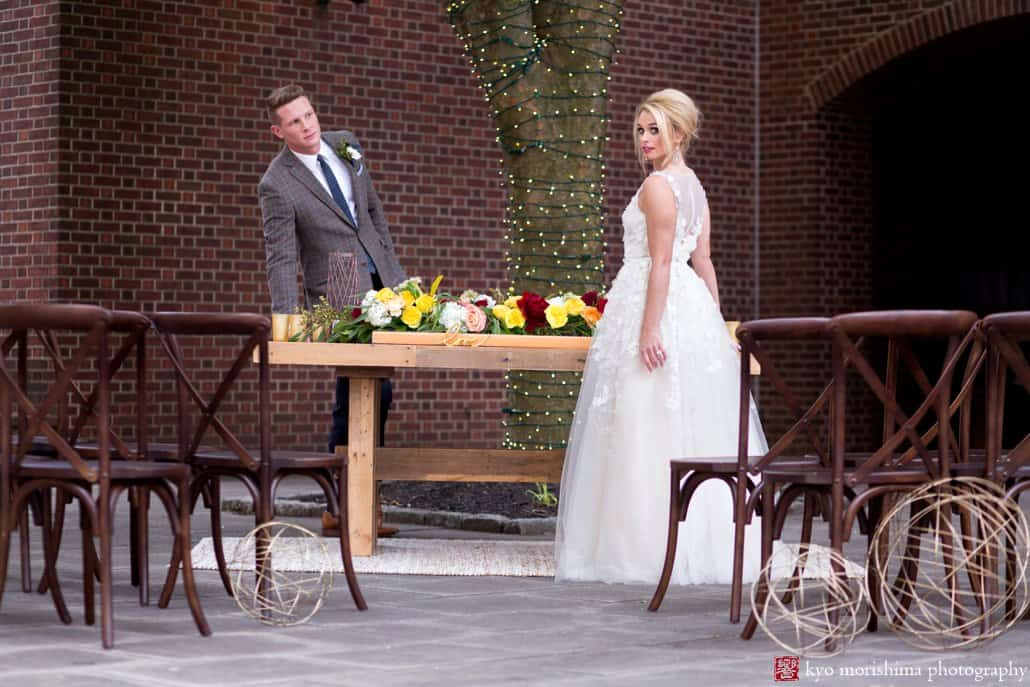 "Bride (wearing BHLDN Ariane wedding gown) and groom stand at West Elm table decorated with maroon and gold flowers by Kristin Rockhill of Details of I Do, at ""Madmen"" wedding shoot at Nassau Inn, photographed by Princeton wedding photographer Kyo Morishima"