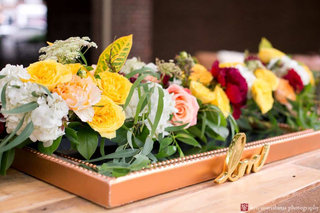 Detail of outdoor table decor with yellow, maroon, and blush roses and peonies and Croton leaf in a copper tray, styled by Kristin Rockhill of Details of I Do, photographed by Kyo Morishima