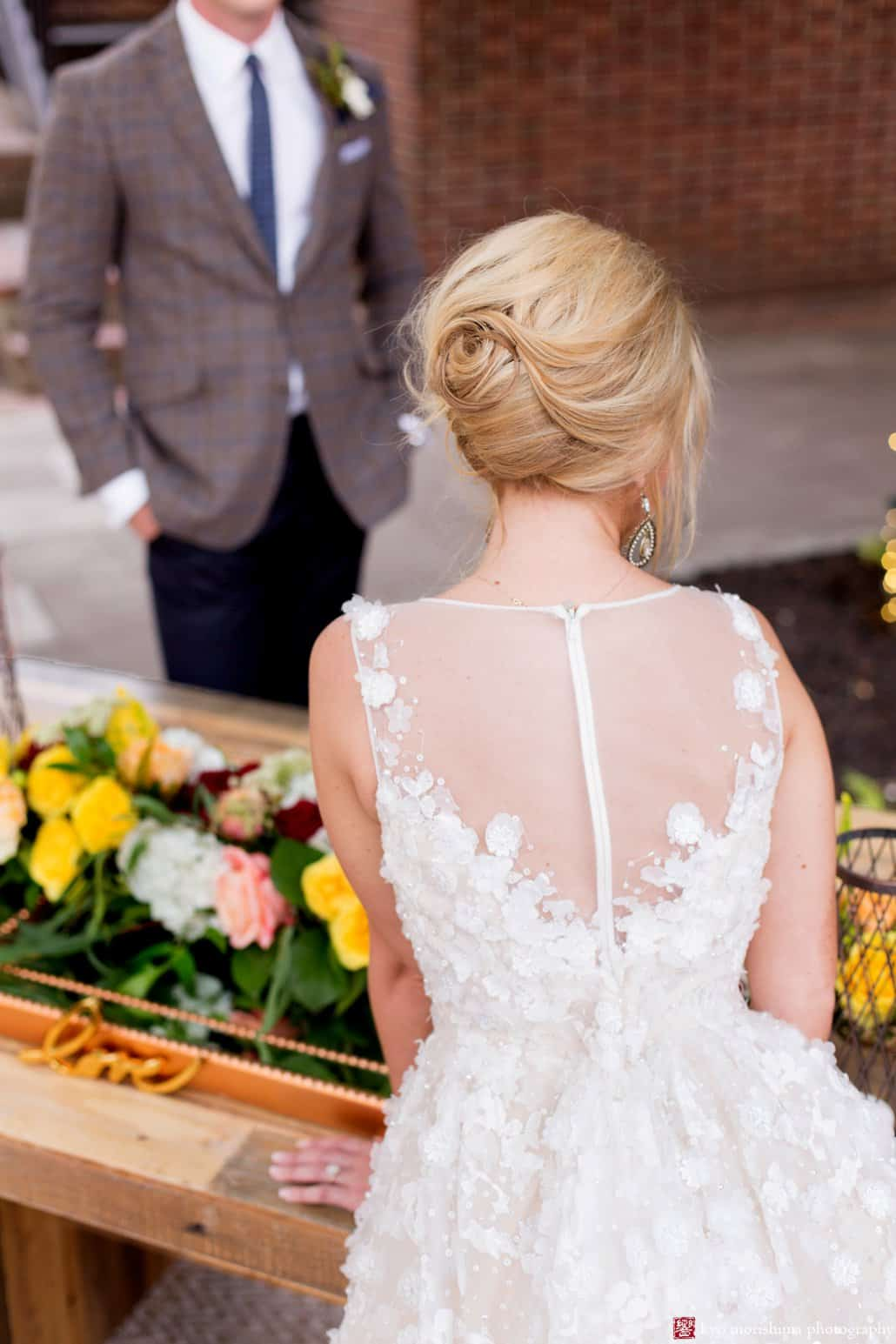 Detail of the back of BHLDN Ariane wedding gown with bride's 1960s updo wedding hair styled by Letitia Kakas, on the Nassau Inn back patio in Princeton, photographed by Kyo Morishima