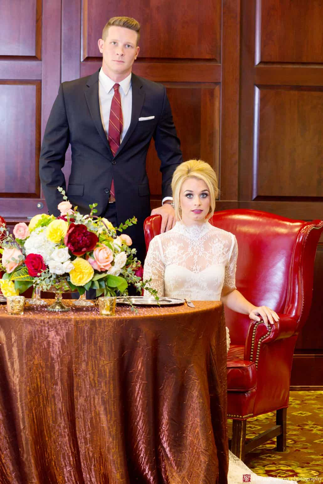"""Maroon, gold and white flower centerpiece in the Nassau Inn ballroom, with bride wearing Bridgette wedding gown from BHLDN, during Nassau Inn """"Madmen"""" photo shoot photographed by Kyo Morishima"""