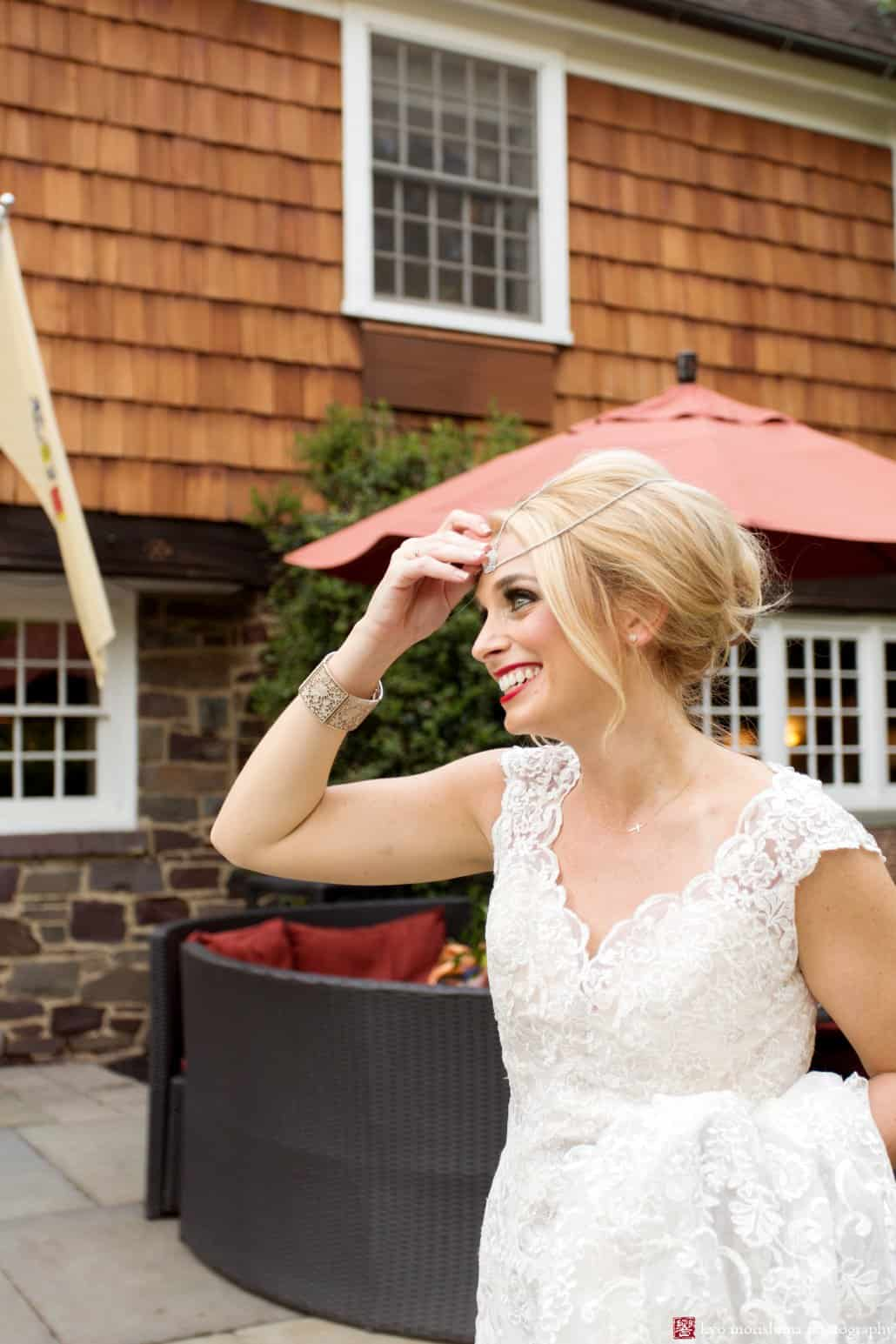 Bride smiles outside Nasssau Inn in Princeton. Bride wears BHLDN wedding gown, 1960s-style updo hair by Letitia Kakas, smoky eyes makeup by Gena Verde Longo. photographed by Kyo Morishima