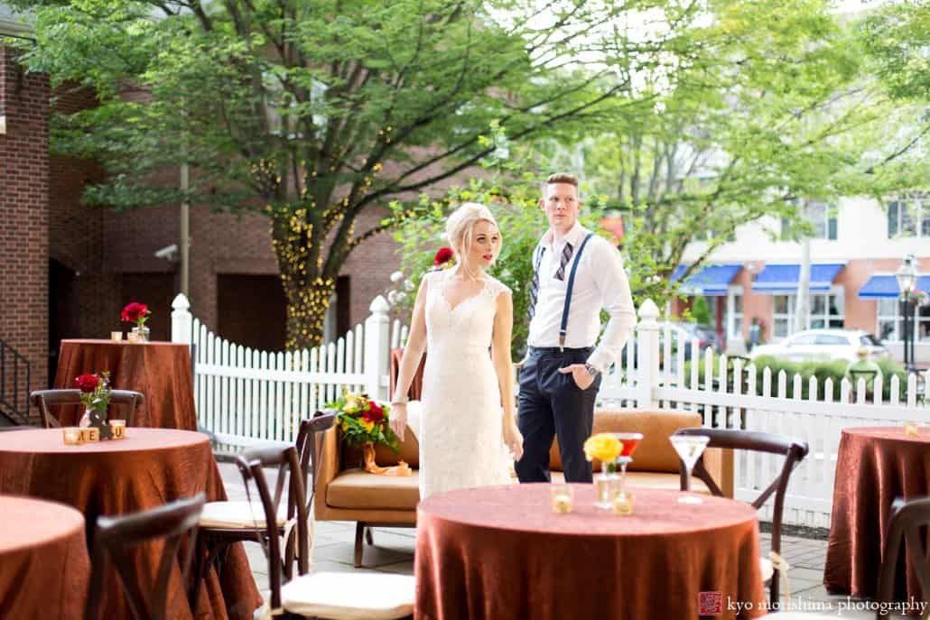 "Bride and groom on patio of Nassau Inn in Princeton during 1960s ""Madmen""-style wedding photo shoot designed by Kristin Rockhill of Details of I Do. Bride wears BHLDN wedding dress,1960s-style updo hair by Letitia Kakas, smoky eyes makeup by Gena Verde Longo. photographed by Kyo Morishima"