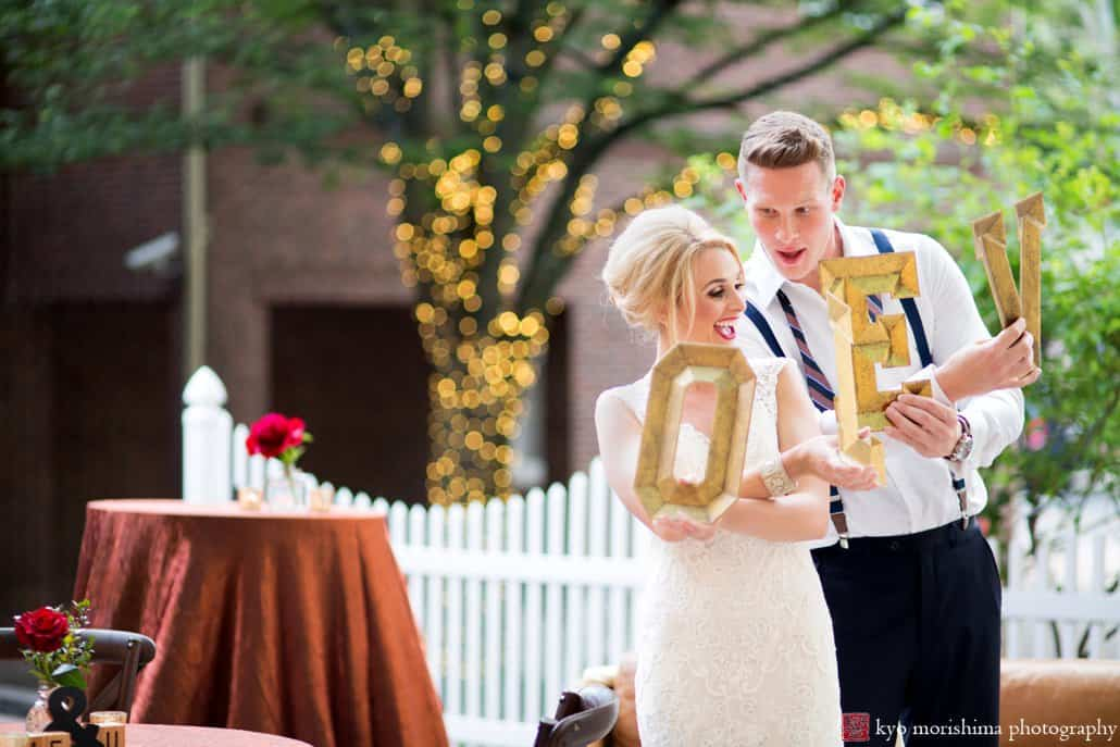 "Bride and groom holding ""LOVE"" letters on Nassau Inn back patio during 1960s-style ""Madmen wedding"" styled shoot, designed by Kristin Rockhill of Details of I Do. Bride wears BHLDN wedding gown. photographed by Kyo Morishima"