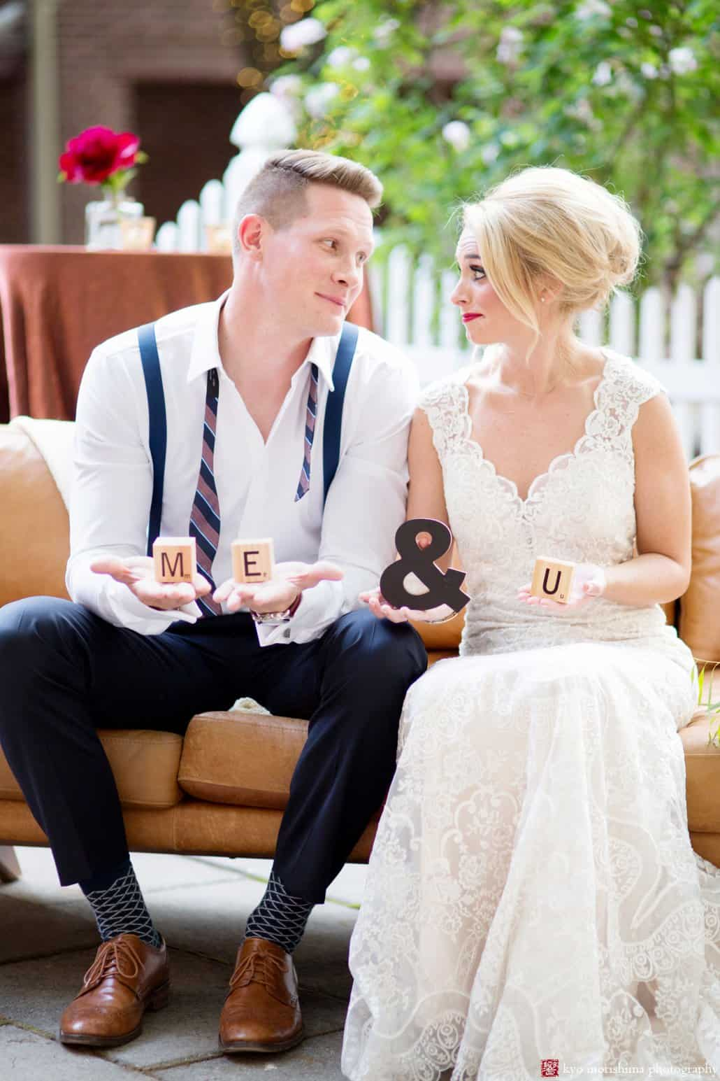"""Bride and groom holding """"me & u"""" props during Nassau Inn """"Madmen weddng"""" styled shoot, designed by Kristin Rockhill of Details of I Do, photographed by Kyo Morishima. Bride wears BHLDN wedding dress."""