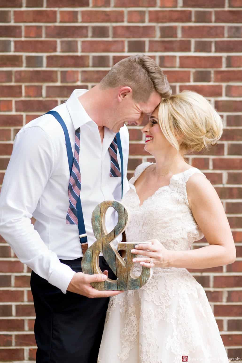 Bride and groom outside brick wall behind Nassau Inn in Princeton; bride wears BHLDN wedding dress and groom holds ampersand sign. Styled by Kristin Rockhill of Details of I Do, photographed by Kyo Morishima