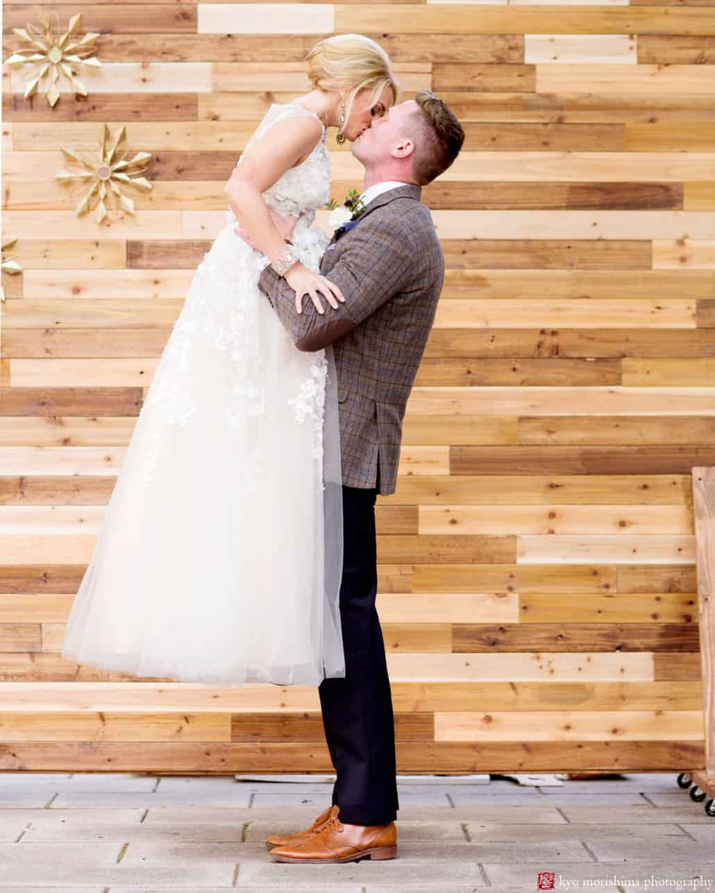"Bride wearing Ariane wedding gown from BHLDN kisses groom in front of wood backdrop at Nassau Inn ""Madmen"" photo shoot styled by Kristin Rockhill of Details of I Do, photographed by Kyo Morishima"