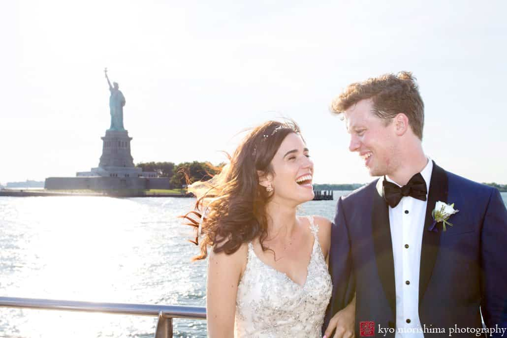 Bride and groom laugh together with Statue of Liberty in the background, photographed by Kyo Morishima
