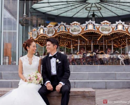 Bride and groom sit in front of Brooklyn waterfront carousel for wedding portrait photographed by Kyo Morishima