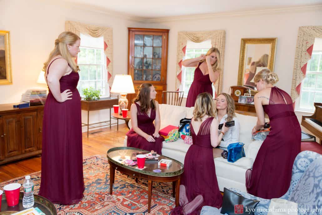 Bride getting ready in the living room surrounded by her bridesmaids wearing maroon Amsale dresses, photographed by Kyo Morishima