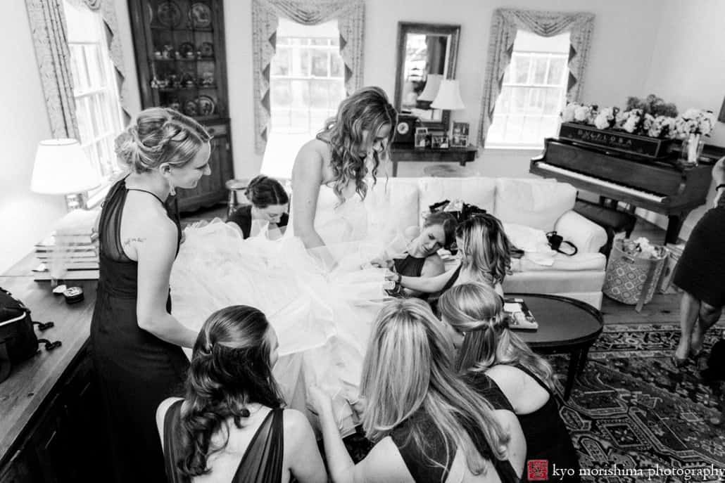 Bride puts on Pronovias wedding gown, surrounded by bridesmaids in the living room