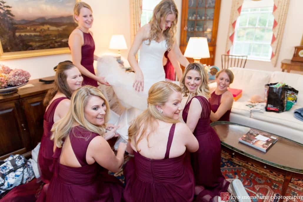Bridesmaids glance back at ringbearer and smile as they help bride get dressed in Pronovias wedding gown