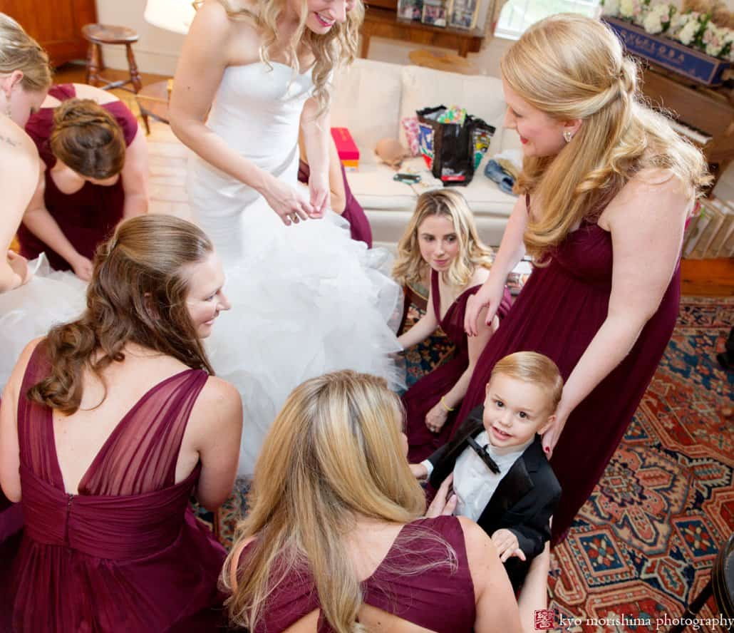 Ringbearer looks up at camera as bride and bridesmaids get ready