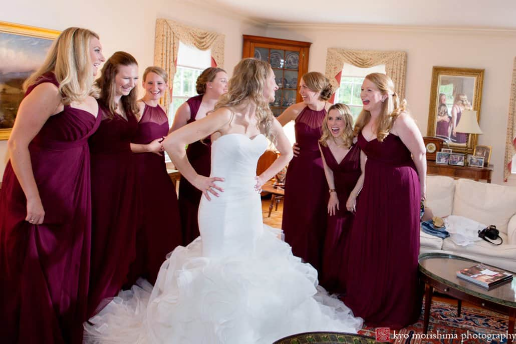 Bride wearing Pronovias laughs with bridesmaids wearing Amsale just after they've finished getting ready in Princeton living room
