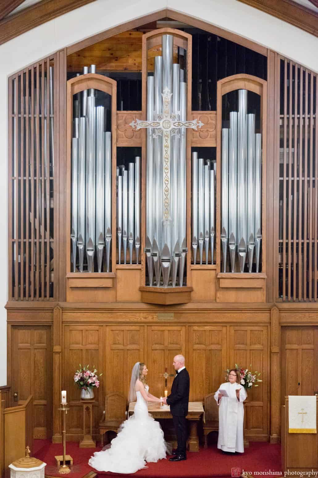 A wide view of bride and groom at the altar framed by organ pipes, photographed by Princeton United Methodist Church wedding photographer Kyo Morishima