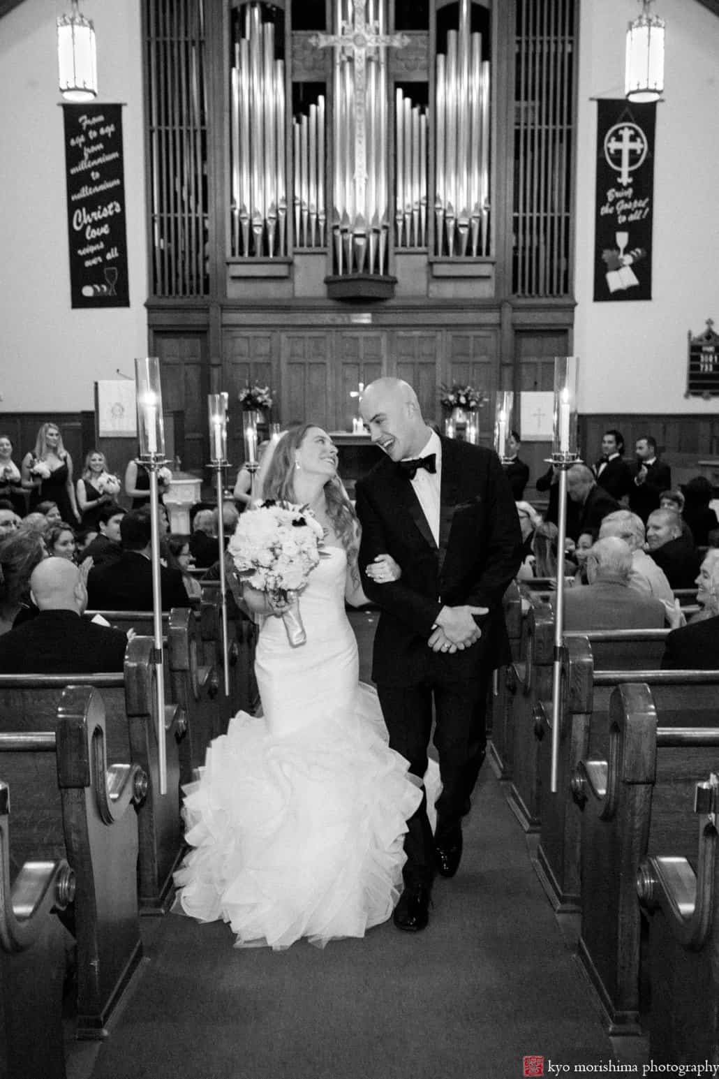 Bride and groom glance happily at each other as they depart Princeton United Methodist Church wedding