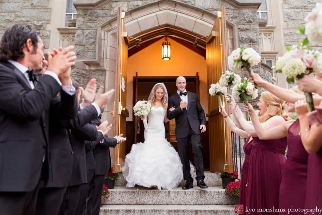 Bride and groom emerge happily from Princeton United Methodist Church wedding with bridesmaids and groomsmen clapping