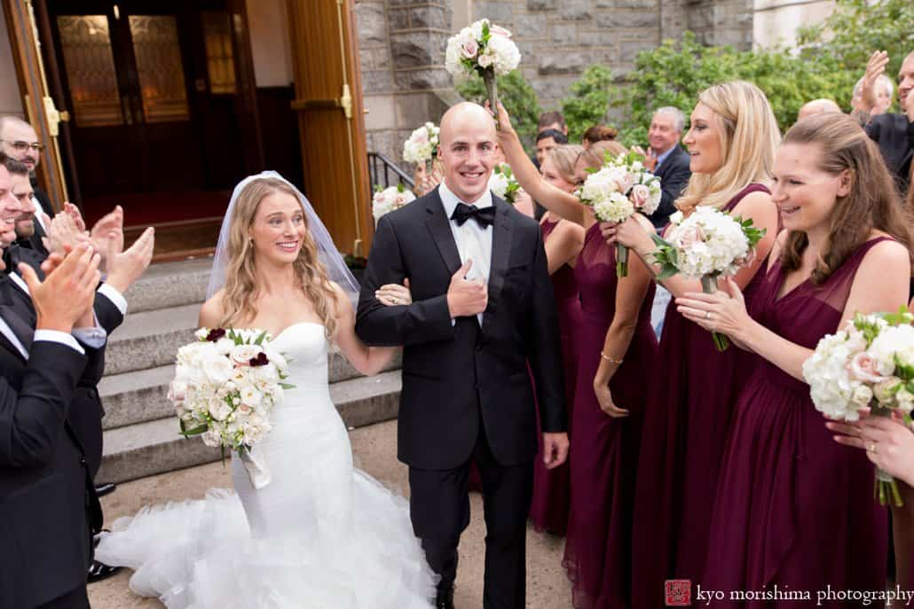 Bride and groom smile happily as bridesmaids cheer their exit from Princeton United Methodist Church wedding ceremony