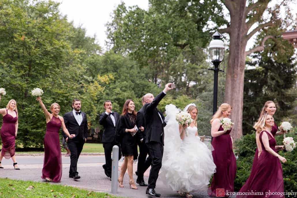 Groom takes a selfie as wedding party walks to wedding portrait location on Princeton University campus