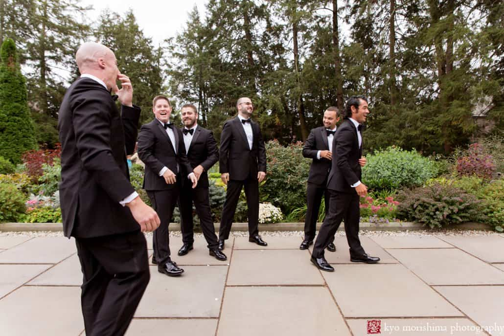 Groom and groomsmen laugh during Prospect Gardens wedding portrait session in October