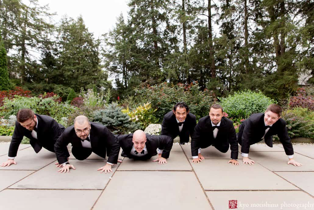 Groom and groomsmen do push-ups during wedding portrait session at Princeton's Prospect Gardens