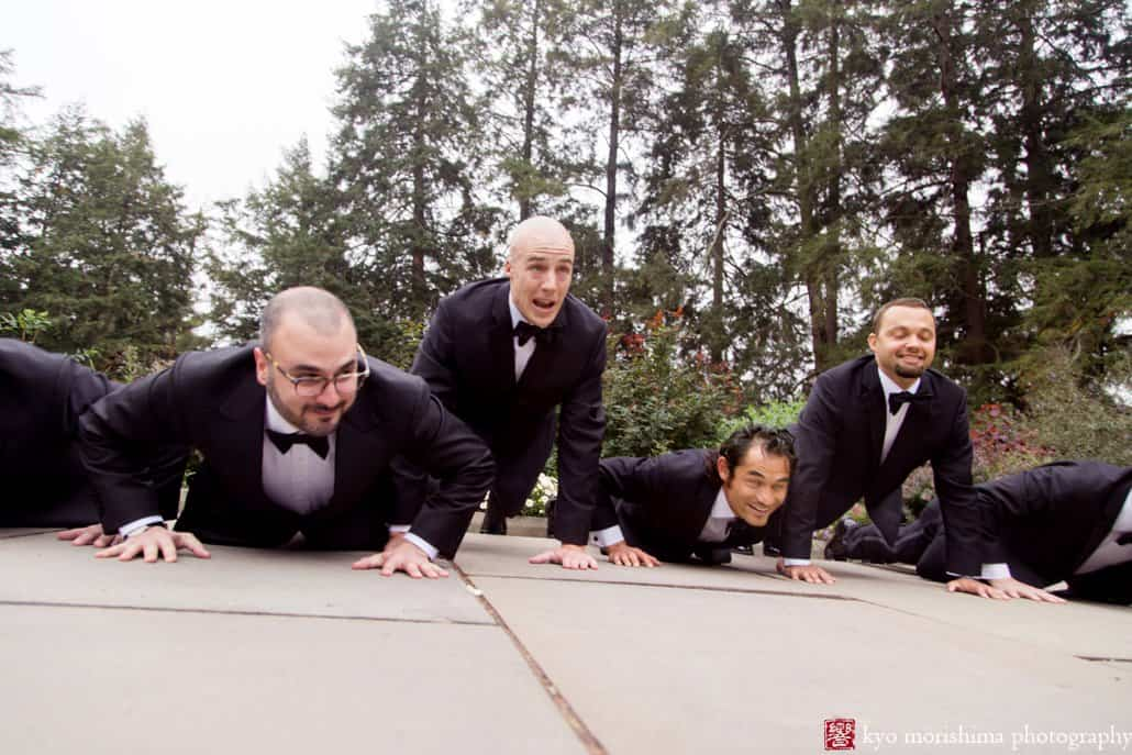 Groom rises above groomsmen while doing push-ups during wedding portrait session at Prospect Gardens