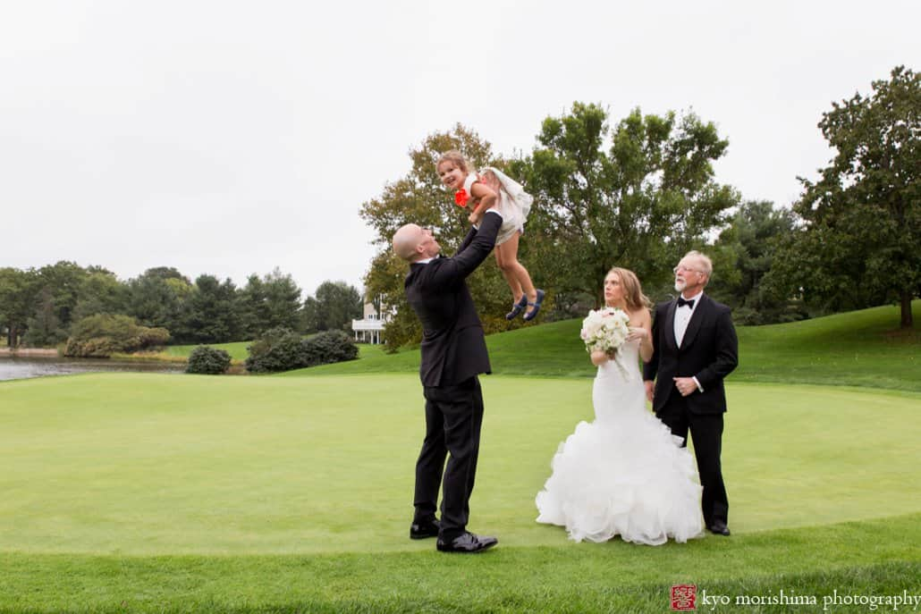 Groom lifts flower girl during family portrait session on the golf course at Cherry Valley Country Club wedding