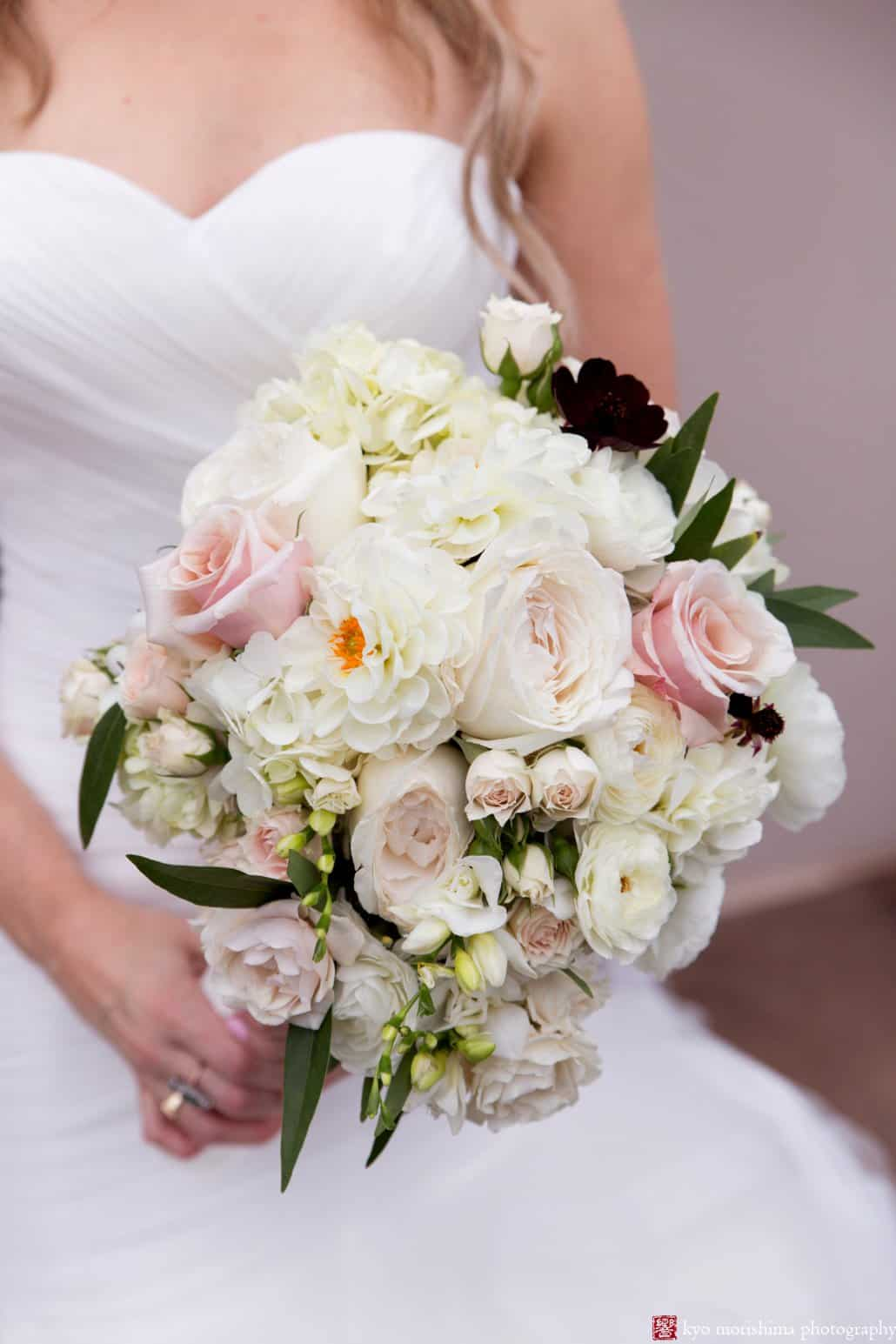 Bride holds white and pale pink rose wedding bouquet by Princeton florist Viburnum