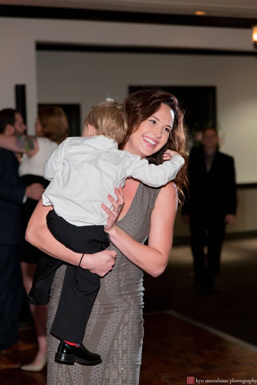 Mom carries tired ring bearer during Cherry Valley Country Club wedding reception