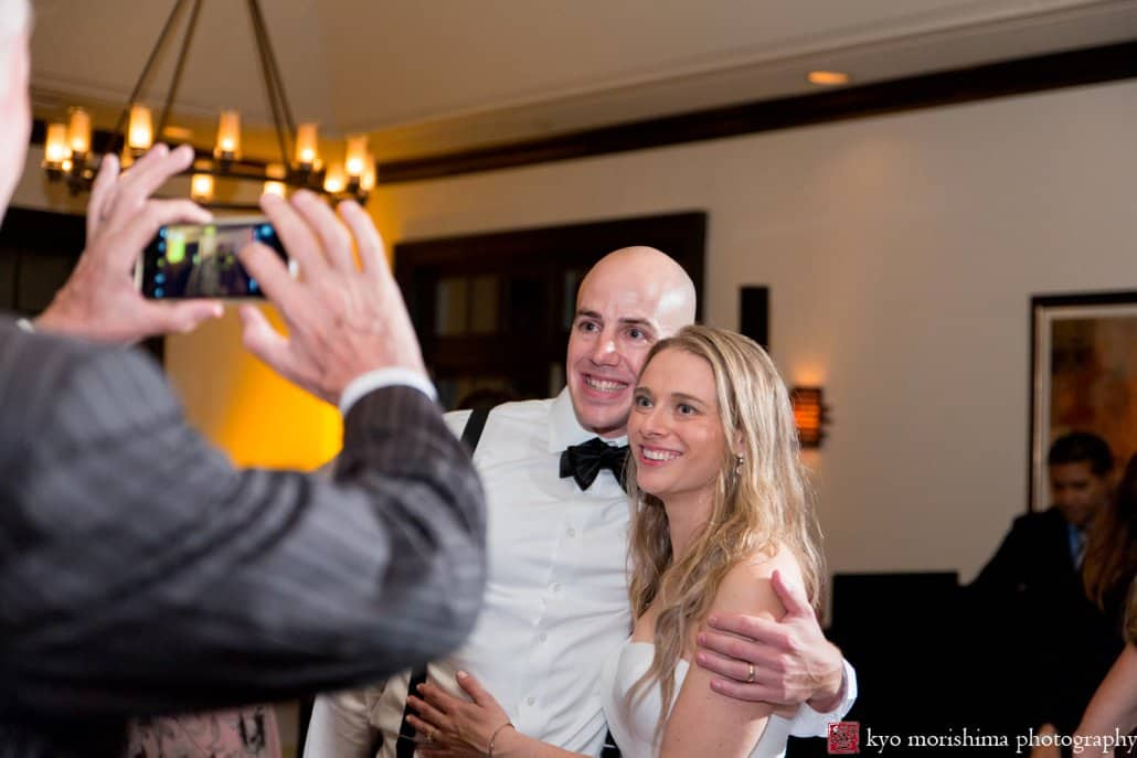 Guest snaps a photo of bride and groom during Cherry Valley Country Club wedding