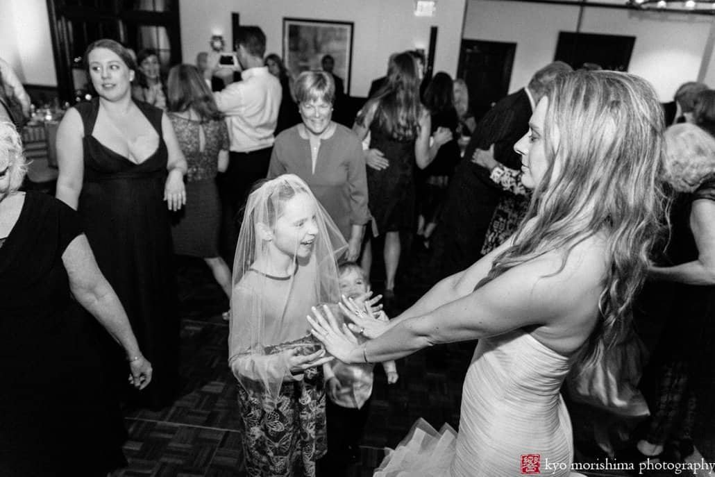 Bride and young guest dance together to music by 74 Events at Princeton wedding reception at Cherry Valley Country Club