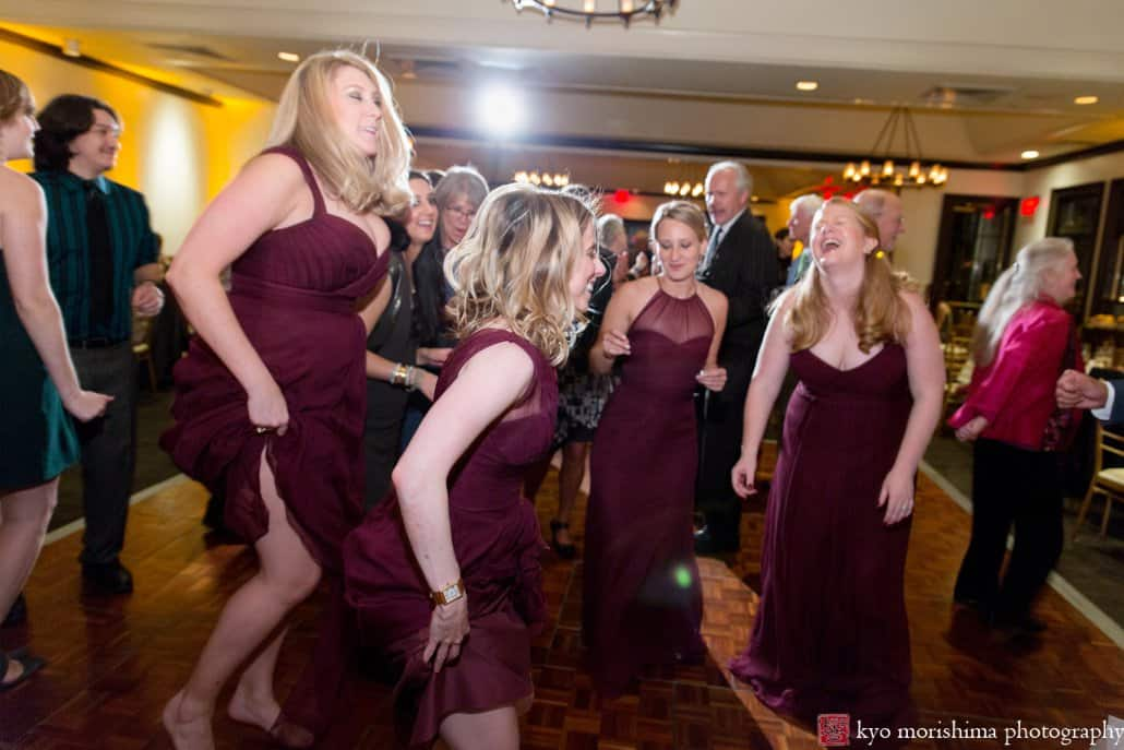 Bridesmaids wearing maroon Amsale dresses dance riotously during Cherry Valley Country Club wedding reception
