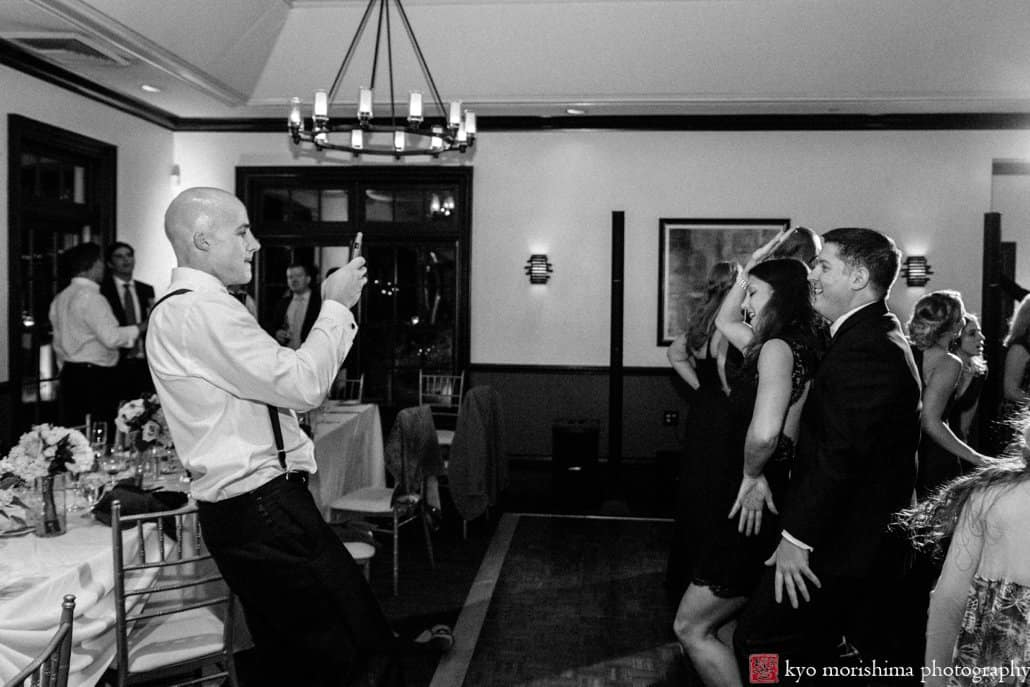 Groom photographs wedding guests cavorting during Cherry Valley Country Club reception