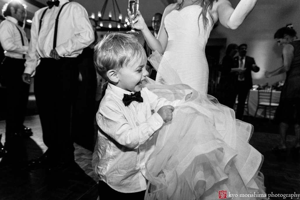 Ring bearer laughs as he grabs Pronovias wedding gown ruffles during Cherry Valley Country Club wedding reception