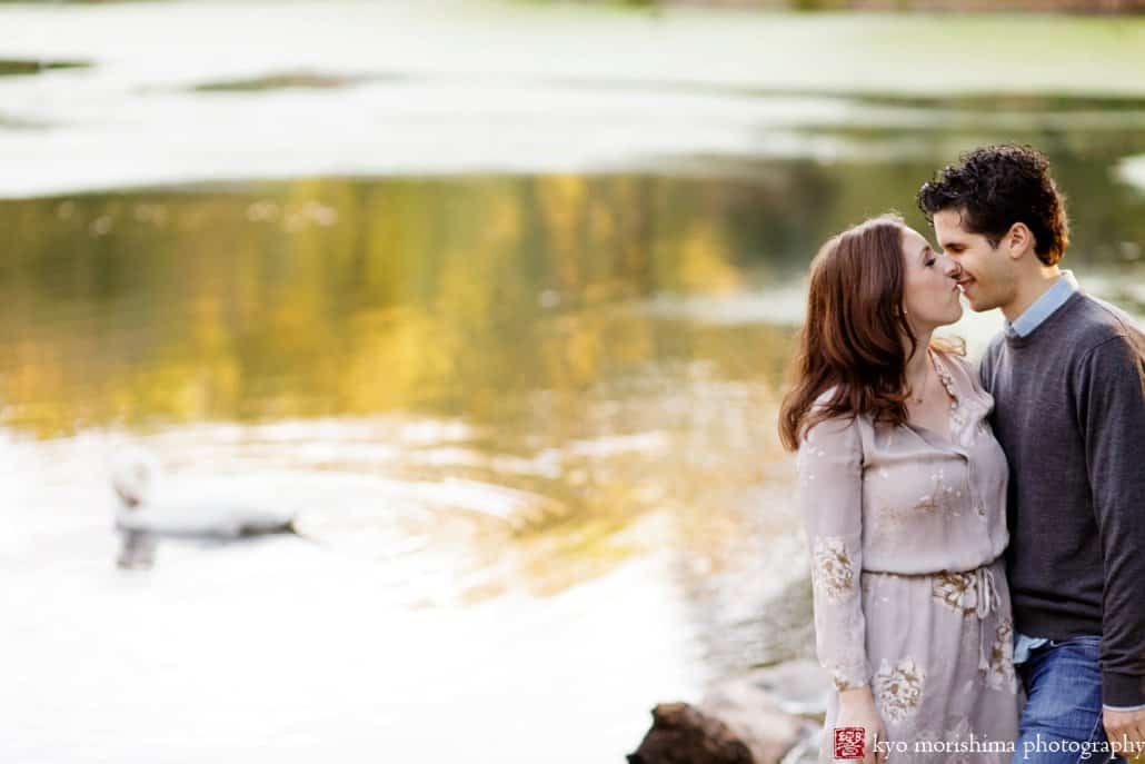A couple kisses with Prospect Park lake in the background, photographed by Brooklyn wedding photographer Kyo Morishima