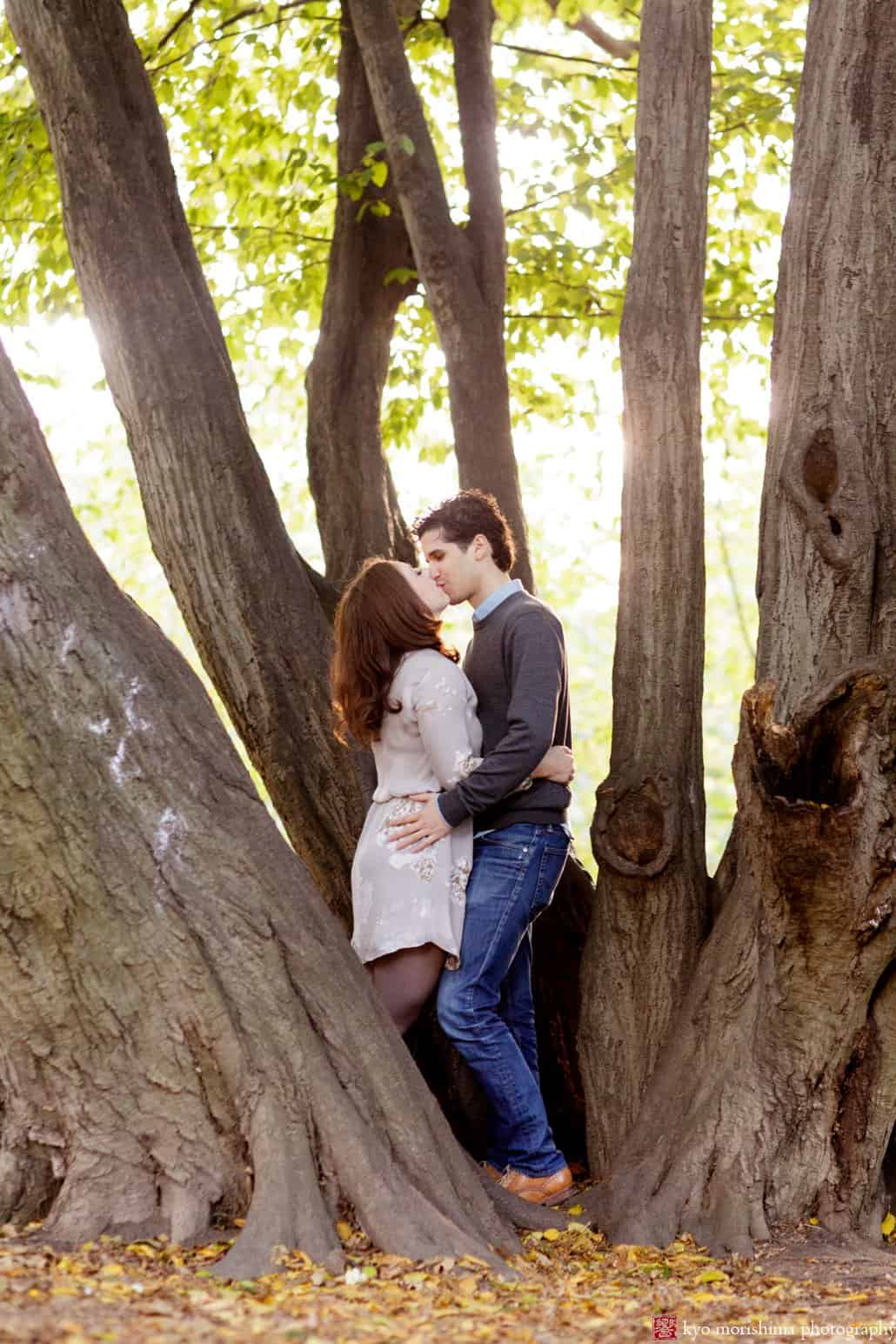 Prospect Park engagement photo: couple kisses while standing among tree trunks, photographed by Kyo Morishima