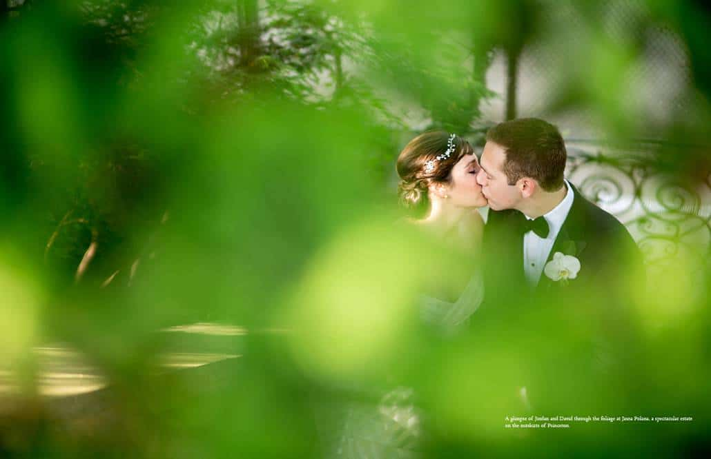 Jasna Polana wedding photo: bride and groom kiss on staircase near the tennis court, with greenery in the foreground