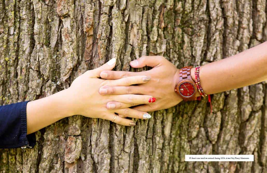 A couple clasp hands around a big oak tree trunk; the woman wears a vibrant gel manicure with a different finish on each fingernail.