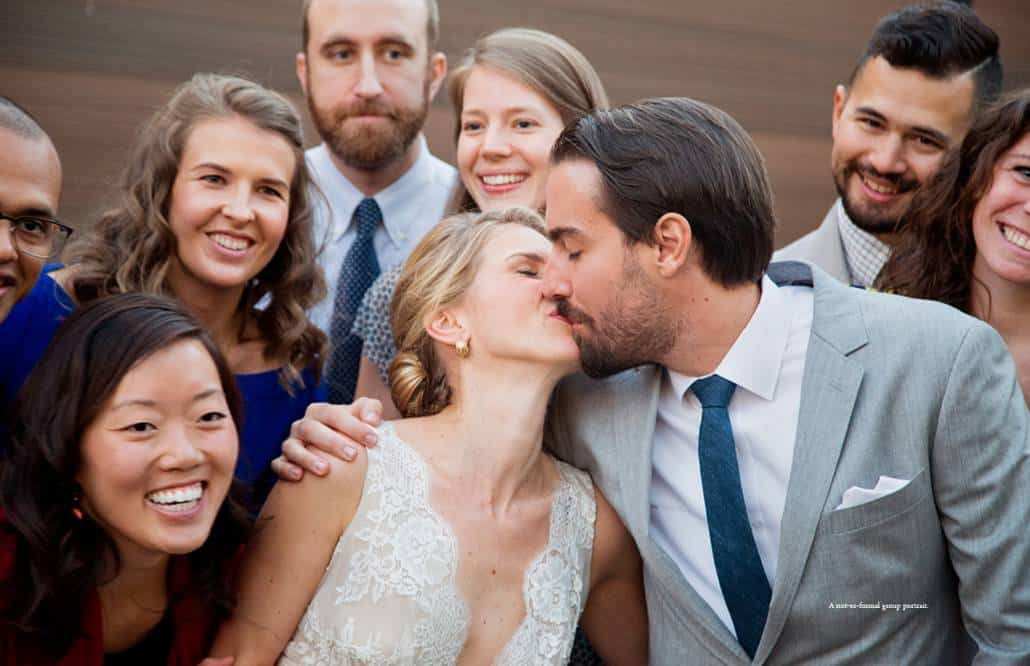 A very informal group portrait with the bride and groom kissing and surrounded by their friends at a Green Building wedding in Brooklyn
