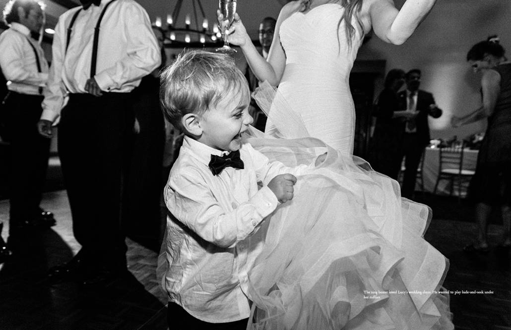 Ringbearer plays hide and seek in the ruffles of bride's Pronovias wedding gown