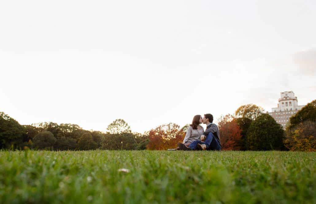 Prospect Park sunset engagement picture with couple kissing in the midground