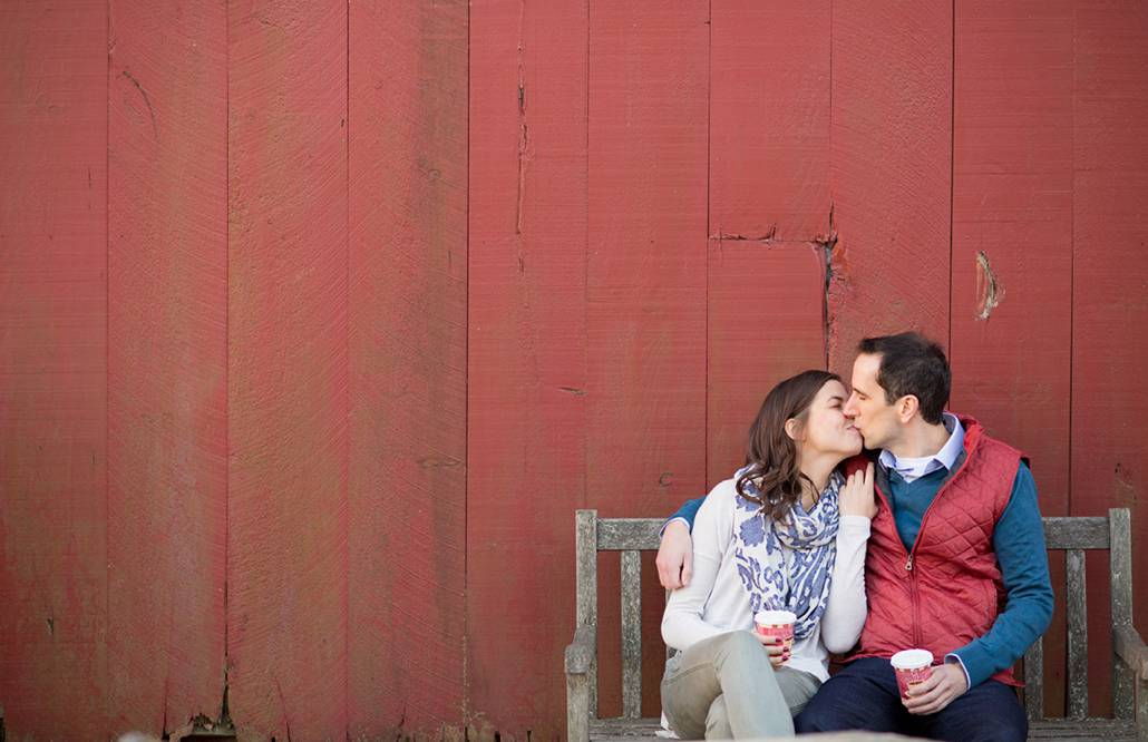 Candid engagement photographer in New Jersey: couple sit on a bench and kiss in front of a red barn at Terhune Orchards in Princeton