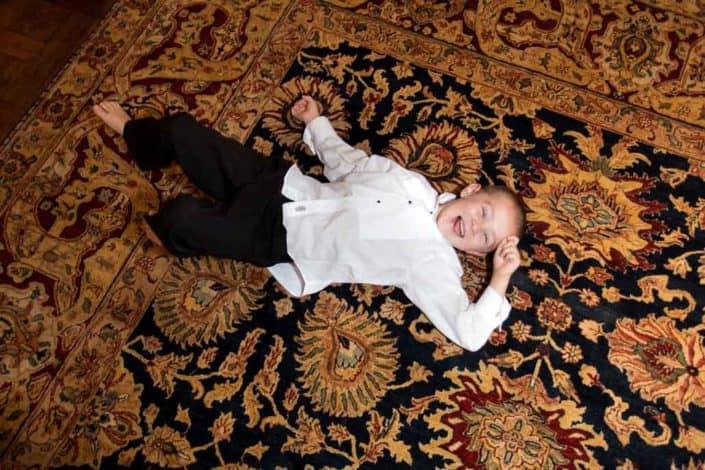 Ring bearer rolling around on a floor during fall Jasna Polana Princeton NJ wedding reception