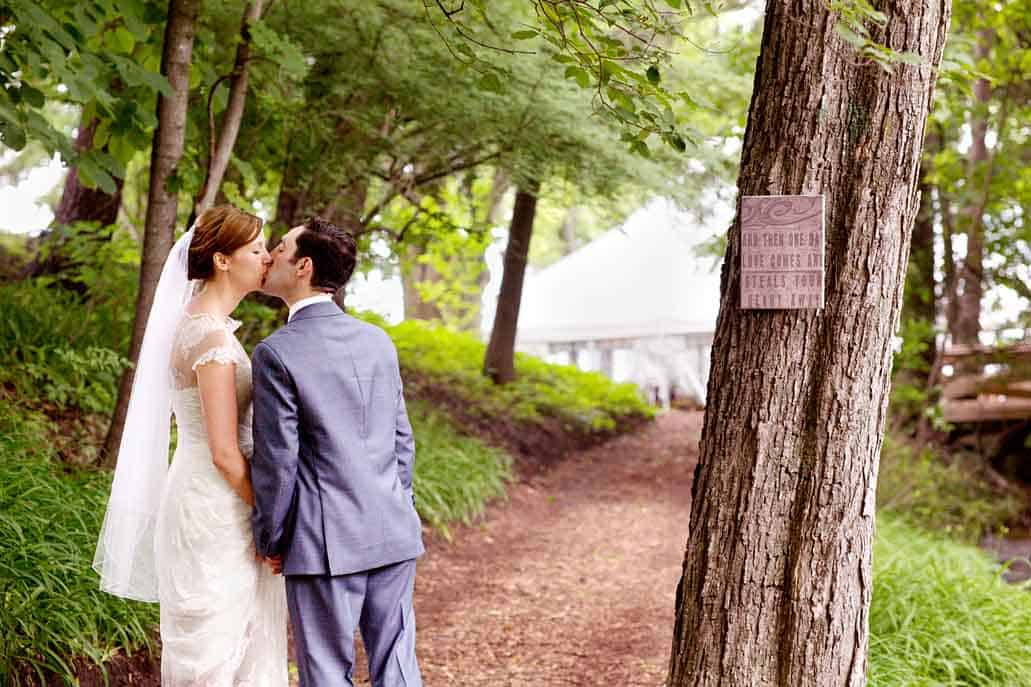"""Lake Geneva rustic backyard wedding portrait with sign saying """"And then one day love comes and steals your heart away""""."""