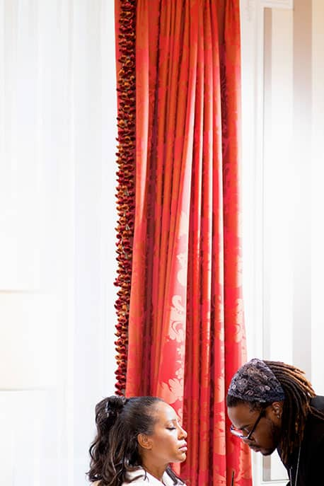 Bride getting ready for her wedding in a suite with big window and a red curtain in the St. Regis Hotel, NY
