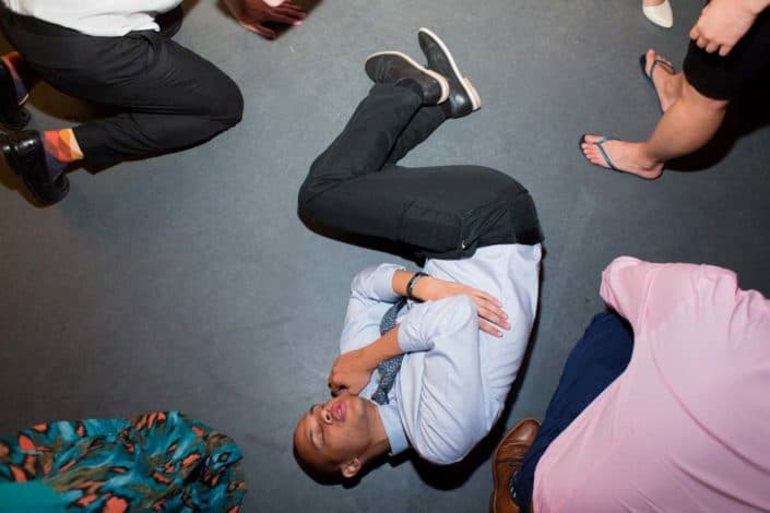 A wedding guest lies down on a dance floor during a wedding reception at Green Building Brooklyn, NJ